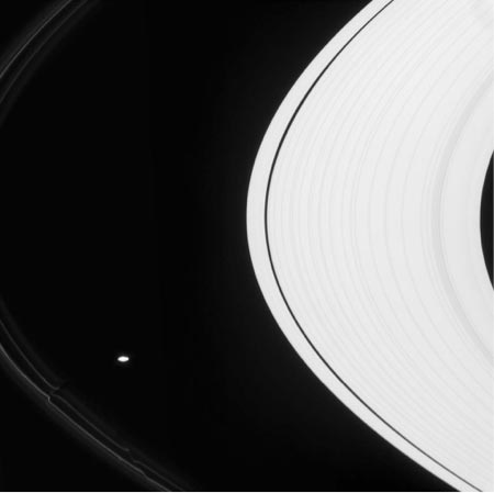 Image of Black and white image showing spatial relationship of barely visible F ring, Saturn's oblong Prometheus satellite, and Saturn's rings.