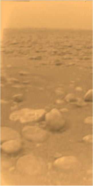 Image of Surface of Titan enveloped in an orange haze of smog.