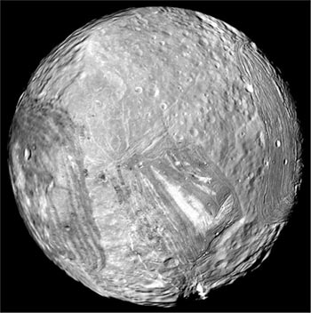 Image of Miranda, shows a whitish chevron or check mark on the lower right of the moon.