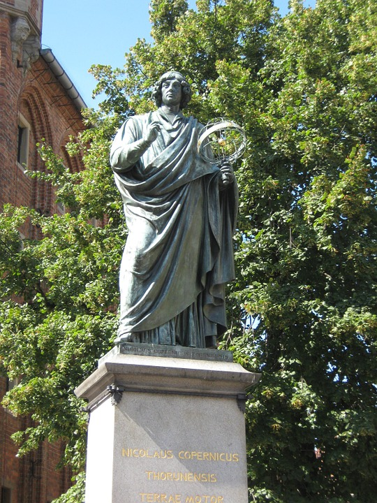 Image of a statue of Astronomer Nicolaus Copernicus holding model of Heliocentric Solar System.