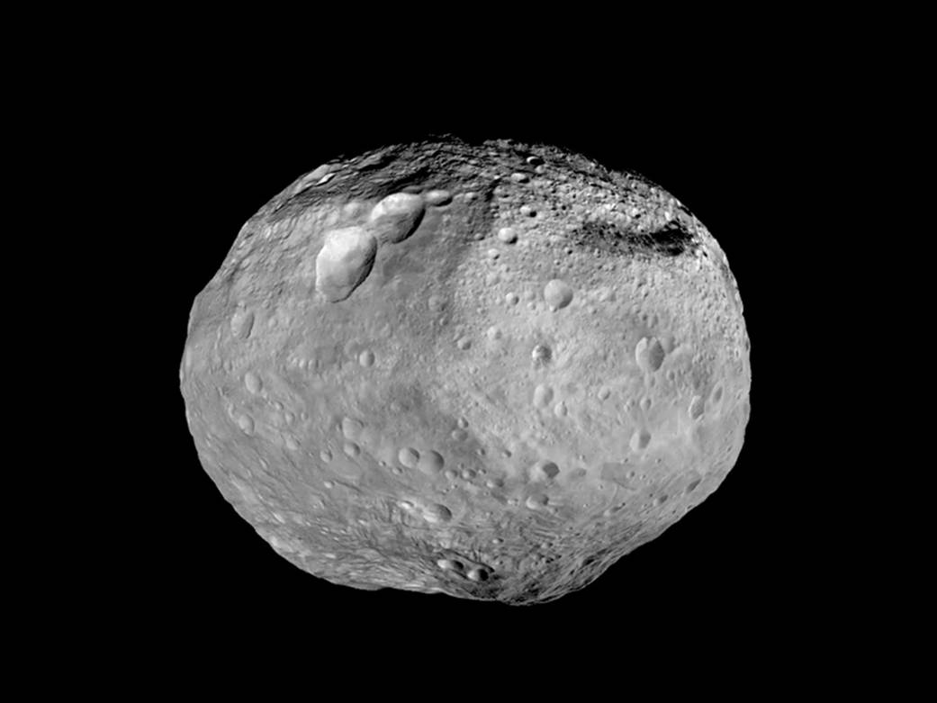 Image of Asteroid (4) Vesta, which is heavily cratered and shaped like a watermelon.