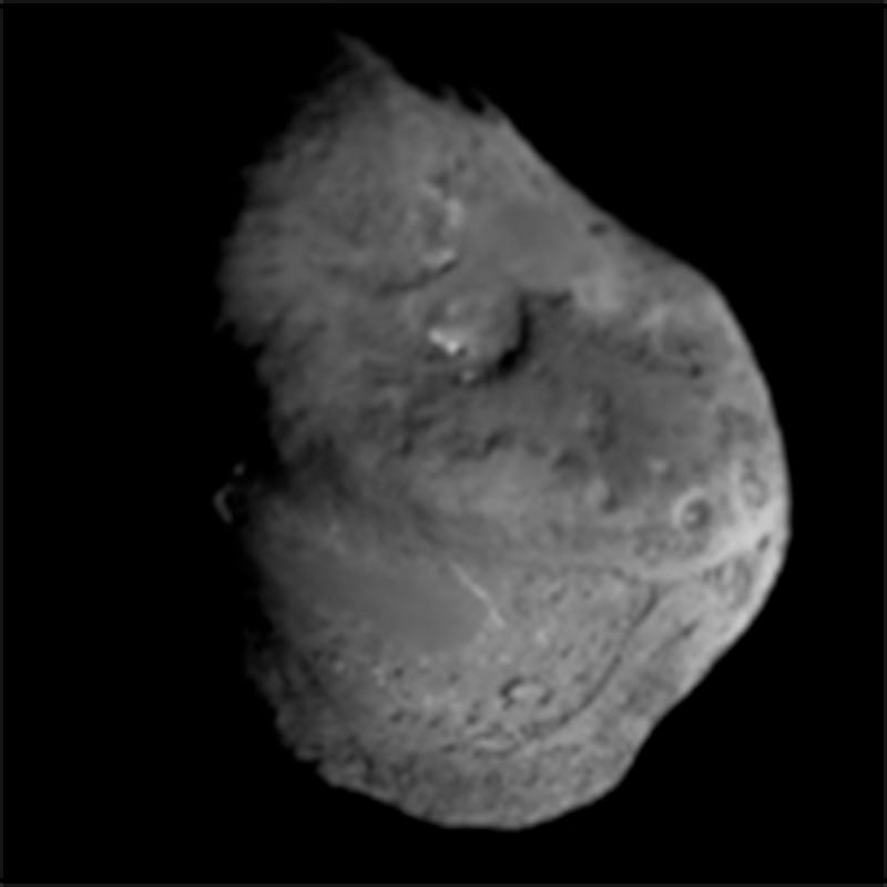 A photograph of the Tempel-1 comet nucleus, taken by the NASA Deep impact spacecraft, which shows an irregular-shaped and impacted body.