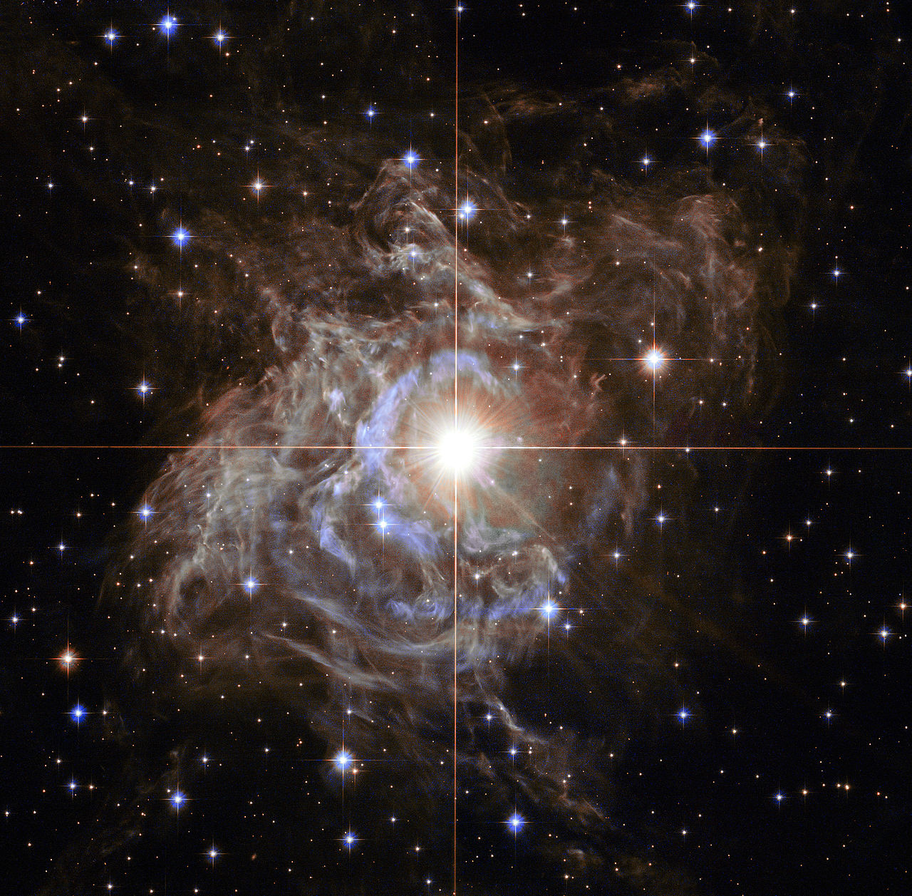 This Hubble image shows RS Puppis, a type of variable star known as a Cepheid variable. As variable stars go, Cepheids have comparatively long periods— RS Puppis, for example, varies in brightness by almost a factor of five every 40 or so days. RS Puppis is unusual; this variable star is shrouded by thick, dark clouds of dust enabling a phenomenon known as a light echo to be shown with stunning clarity. These Hubble observations show the ethereal object embedded in its dusty environment, set against a dark sky filled with background galaxies.