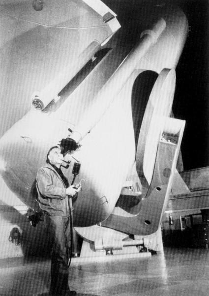 Black and white image of Edwin Hubble standing by the 100-inch Mt. Wilson Telescope at the Mt. Wilson Observatory.