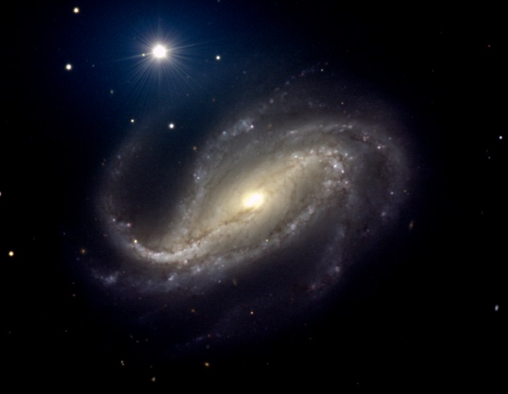 Image of NGC 613, a Barred spiral galaxy, appears like an elongated bar of stars across the Central Bulge.