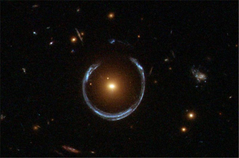The gravity of a luminous red galaxy, center, has gravitationally distorted the light from a much more distant blue galaxy, seen as a horseshoe surrounding the luminous red galaxy. Rings like this are now known as Einstein Rings.