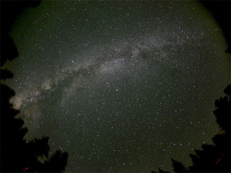 Tthin the broad band of stars are dust lanes within the Milky Way Galaxy.