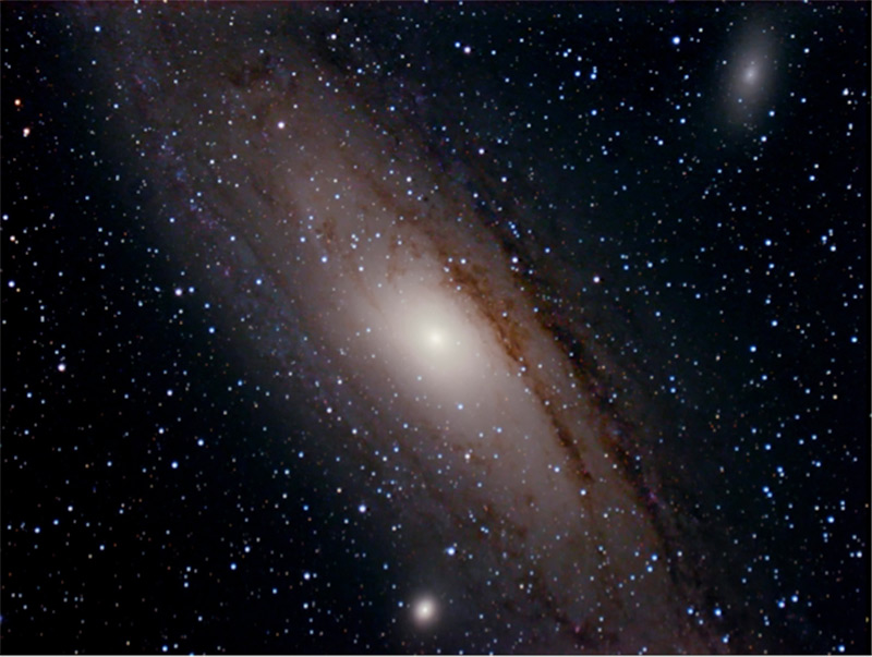 Image of The Andromeda Galaxy with two companion galaxies; dark lanes within a broad band of stars are dust lanes within the Milky Way Galaxy.