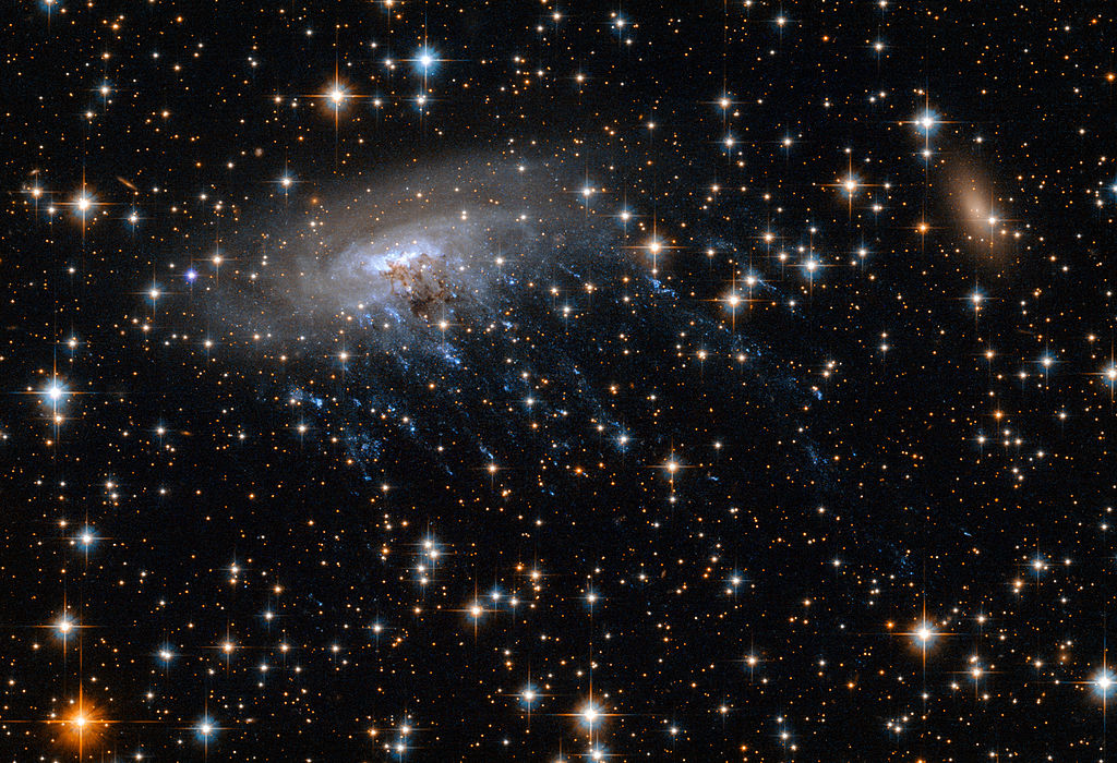 Image shows spiral galaxy ESO 137-001, framed against a bright background as it moves through the heart of galaxy cluster Abell 3627.
