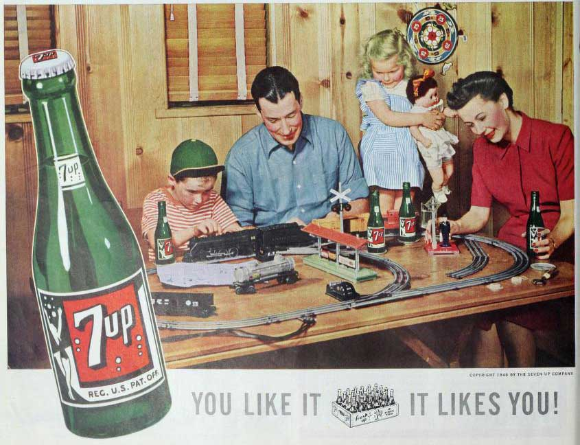 A 7-Up soda advertisement from the mid-twentieth century. The advertisement features a mother, father, son, and daughter playing with a table-top electrical train set and bonding over bottles of 7-Up soda. The advertisement features a large image of a bottle of 7-Up soda in the left margin and features the tagline 'You Like It; It Likes You!' at the bottom of the image.