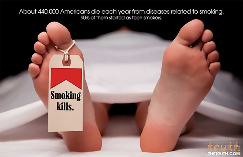 An image of a pair of feat poking out from beneath a white sheet in a morgue. The foot on the left side of the image has a toe tag with the iconic Marlboro Cigarettes red packaging. The toe tag reads 'Smoking Kills.' The text at the top of the advertisement reads ' About 440,000 Americans die each year from diseases related to smoking. 90% of them started as teen smokers.'