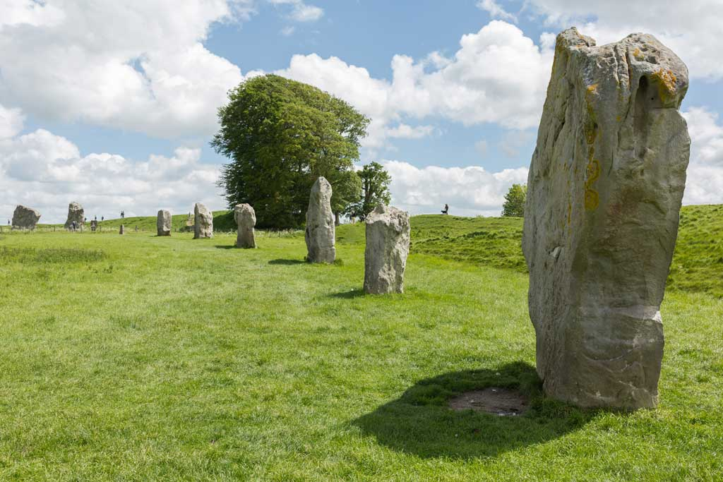 Picture of Avebury Hinges. The perspective captures how the proportionately placed row of large stones serve as a fence across a hilly plain.