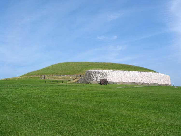 Picture of the Newgrange Monument. The perspective captures the mound-like structure rising from the lush green pasture.