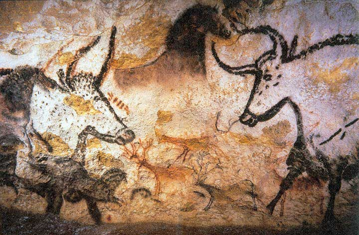 Image from the cave at Lascaux of wild animals. Among the most prominent in image are two bulls outlined in black facing one another. In the middle, there is a chalked entirely in black.