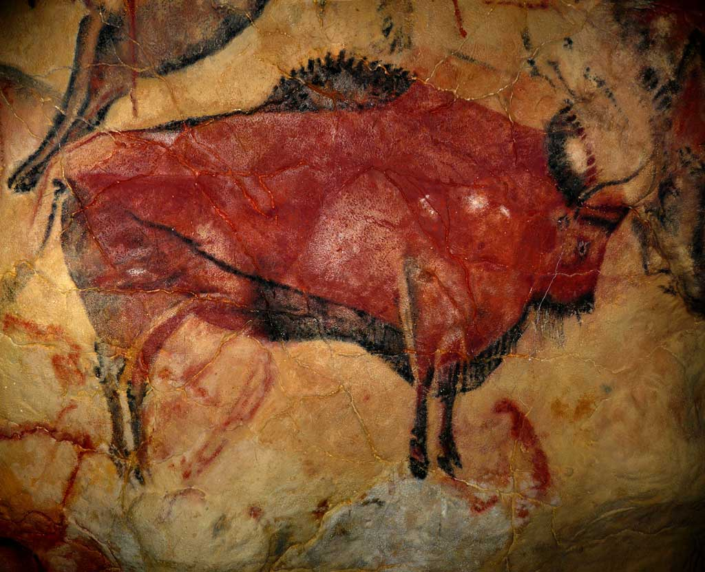 An image of a large red bison facing right, drawn on the light tan color rock wall