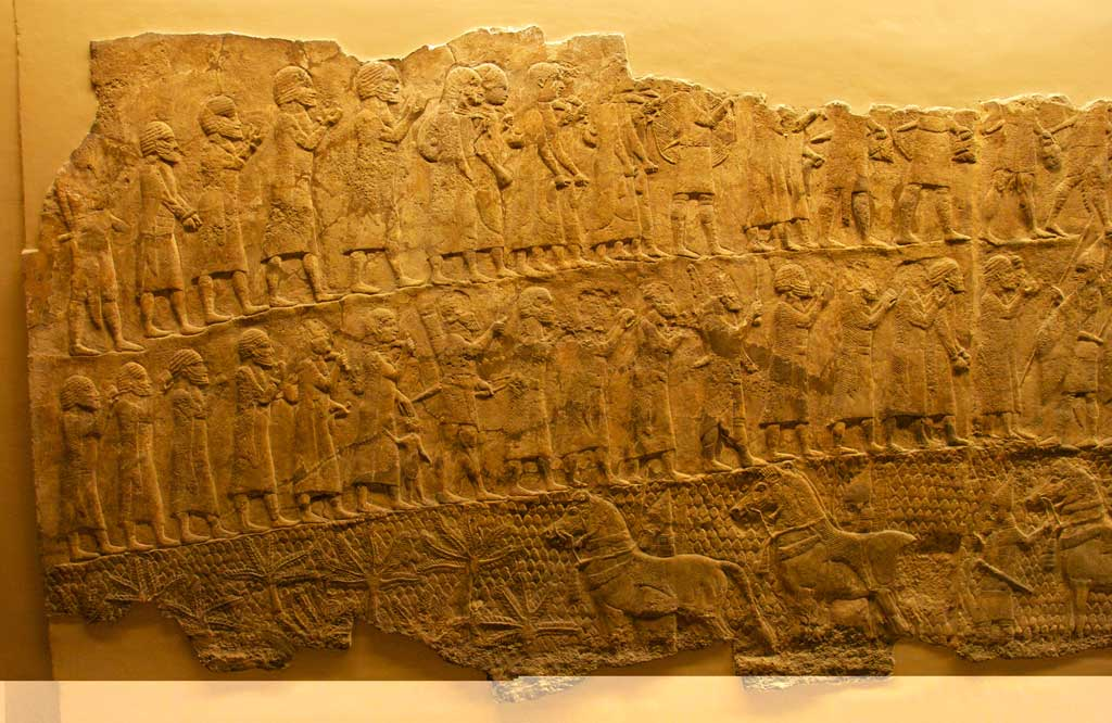 The Lachish Inscription is a reddish stone stele. In this image, the Assyrians lead their war captives away into exile following their victory.