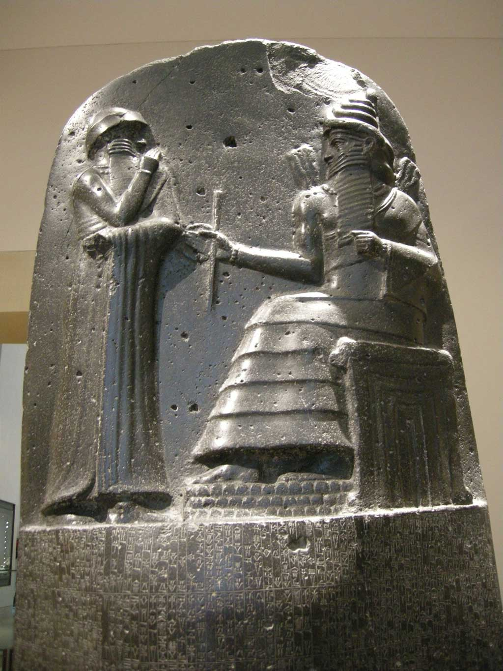 Picture of Hammurabi's Code. A dark cylindrical stone statue with a carving on the upper portion of the Code. Here, one sees a representation of king Hammurabi receiving his law code from the god Shamash who sits before him. Both are two-dimensional in form.