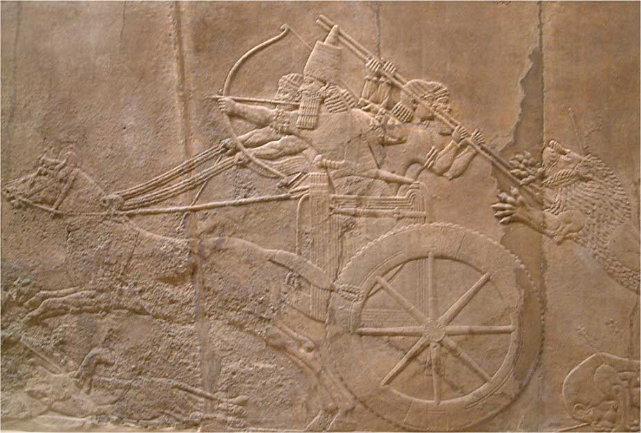 Image of the two-dimensional stone frieze entitled Ashurbanipals Lion Hunt. This particular image depicts the king at the front of his chariot curving his bow, while his soldiers ride in the rear of his chariot spearing a lion.