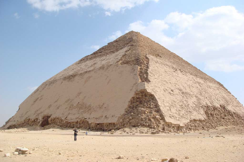 The picture is that of the Bent Pyramid. In this image, a smooth-sided pyramid has a large lower base and a disproportionately smaller triangular top.