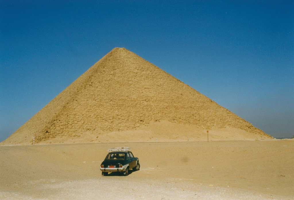 The picture is that of the Red Pyramid. The image is that of a triangular pyramid rising from the ground, Smooth-sided but stony in appearance, traces of the limestone that once covered its surface lay at its base.