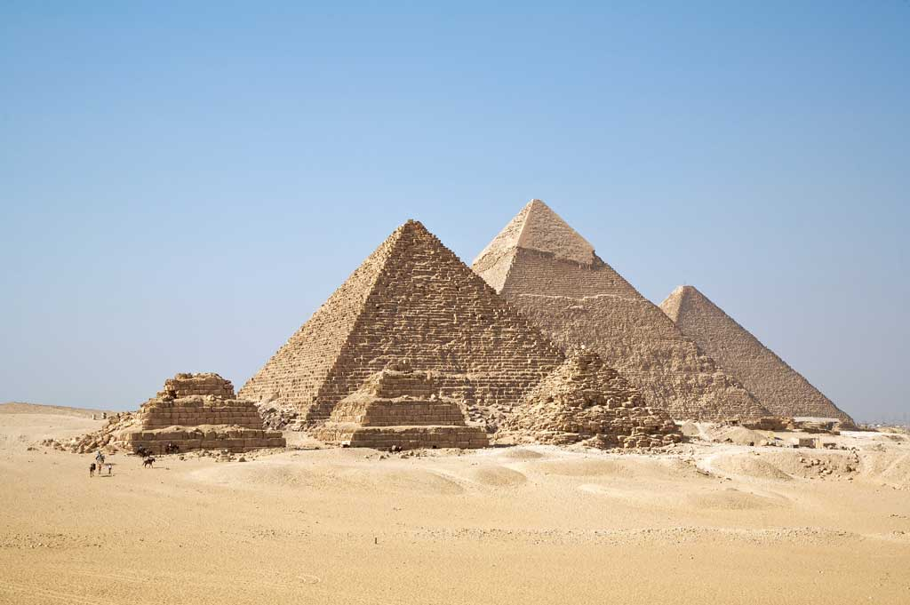 The picture is that of the six Pyramids of Giza. In the background are the three large pyramids of kings Menkaure, Khafre, and Khufu situated in a line. All three are smooth-sided. In front, are three smaller pyramids, of which only one is not a stepped pyramid.