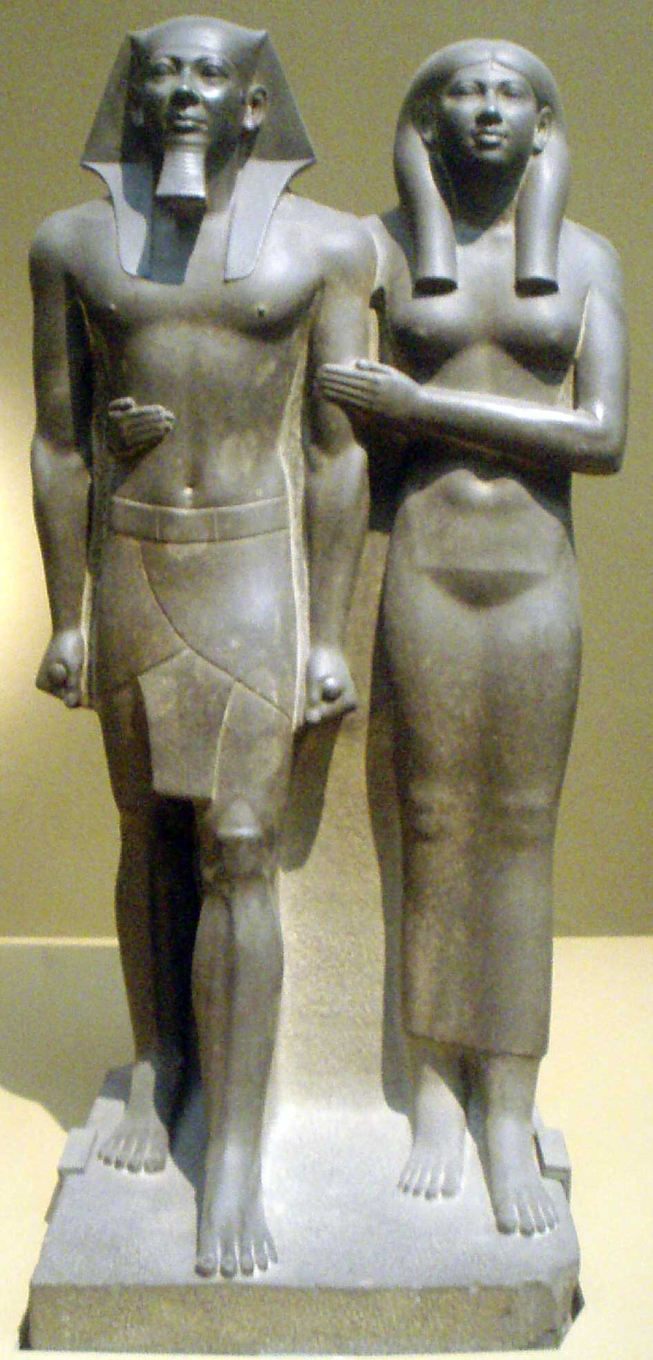 The image is that of the Egyptian king Menkaure and his queen, Khamerernebty II. Hewn from dark stone, both king and queen are stoic in appearance and possess ideal bodies. Although standing shoulder to shoulder, Menkaure's foot steps ahead of his wife to illustrate his superior position.
