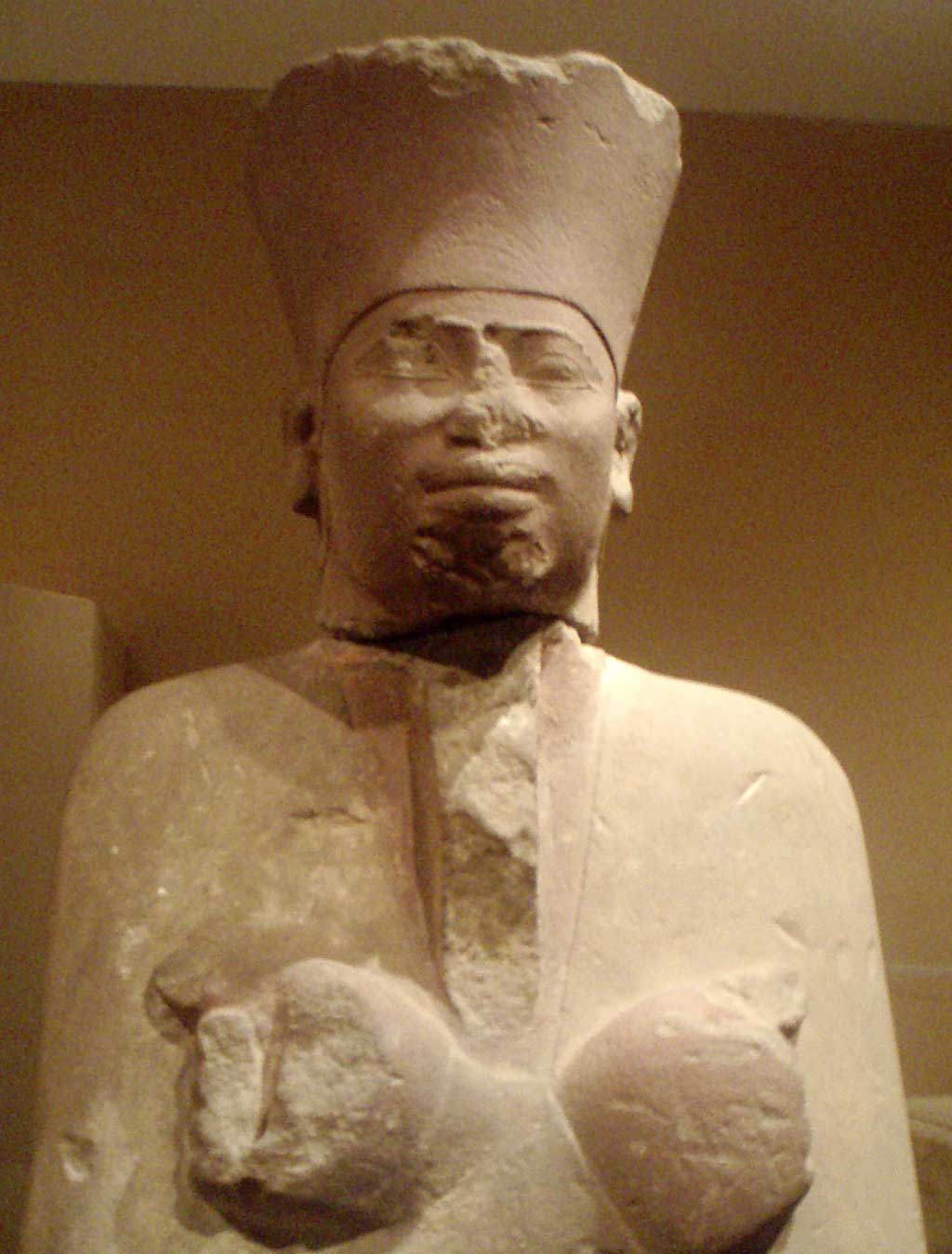 Image of a white sandstone statue of Mentuhotep II. Atop his head he wears the crown of lower Egypt.
