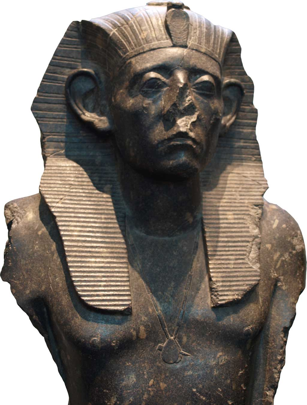 Black sandstone statue of Senusret III wearing the Pharaonic headdress. His nose is missing from the statue, suggesting that it was defaced. His eyes are contemplative and his brow tense, connoting perhaps his recognition of the vicissitudes which have befallen Egypt in prior centuries.