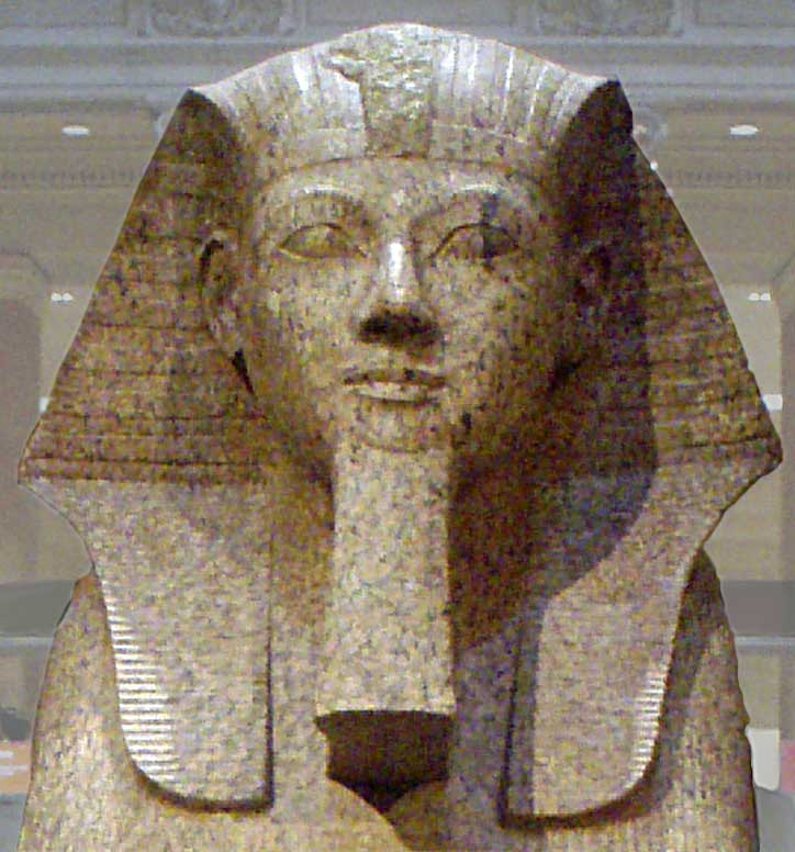 The second picture is also a stone depiction of Hatshepsut. Still expressionless with the royal crown, the queen is now featured with a false beard to connote her pharaonic authority.