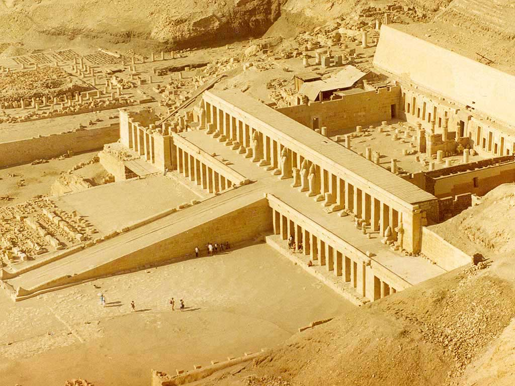 The picture is an aerial view of the massive temple of Hatshepsut. From overhead, there appears a long ramp leading up to a columned entrance way. An open courtyard where the temple precincts once presided.