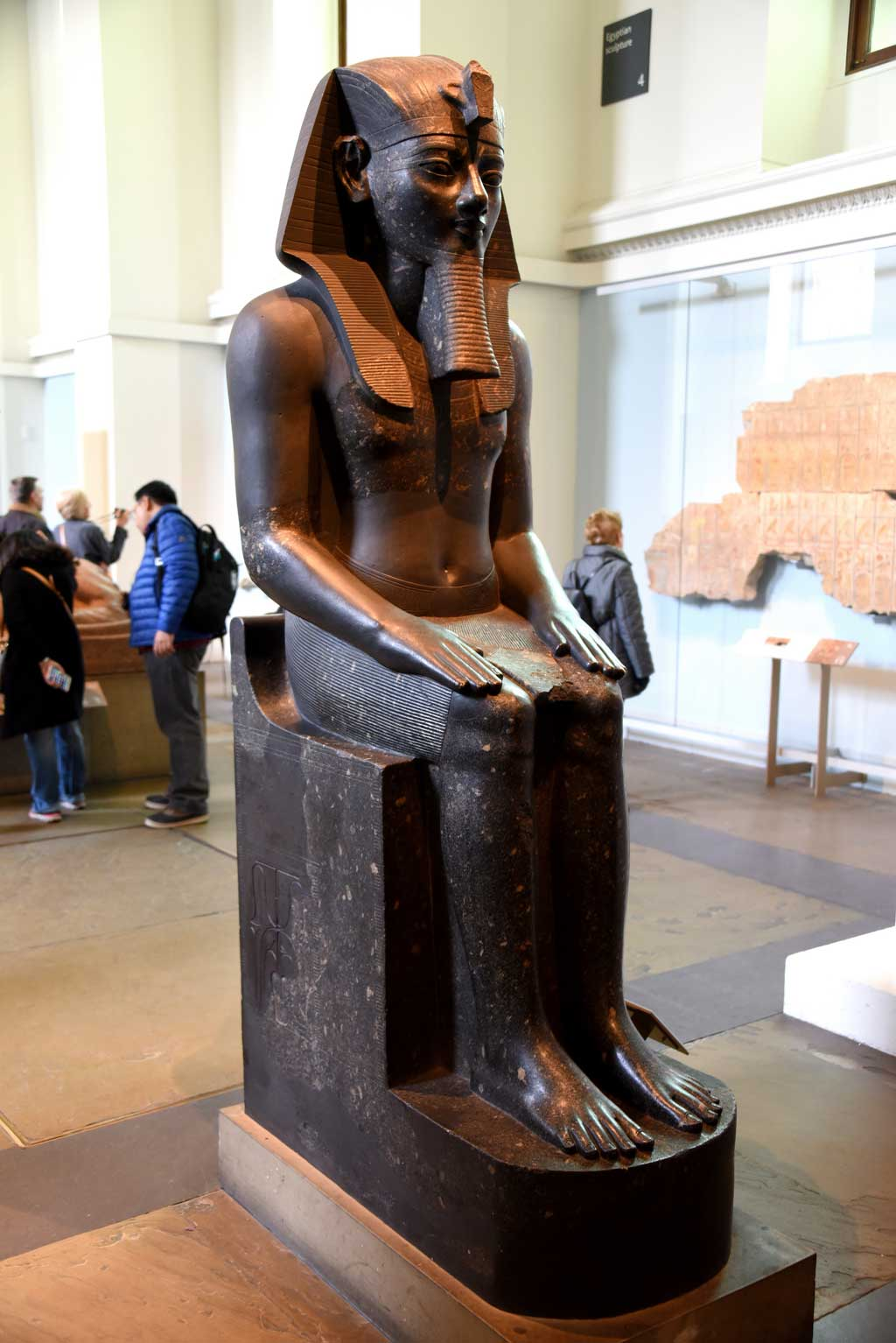 The picture is of a seated Amenhotep III, carved out of black stone. Here, the king sits while looking straight ahead, with hands placed flatly on his bent knees.