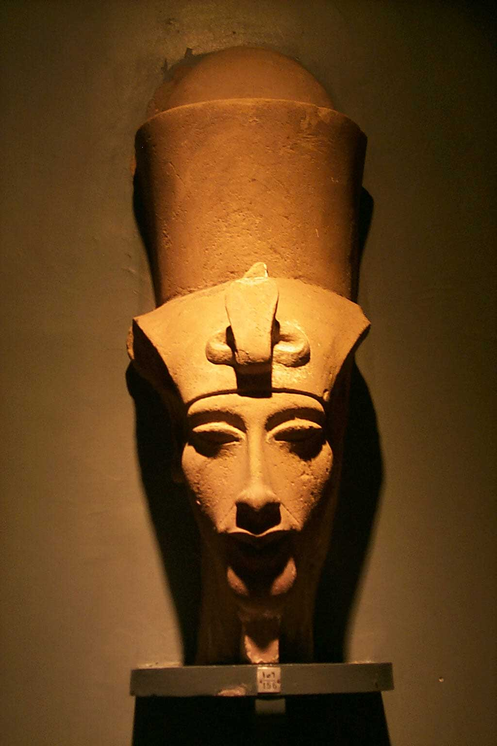 The picture is of a stone bust of Pharaoh Akhenaten. Here, the king is depicted with a slender face and extended facial features. Atop his head is the double crown of Egypt.