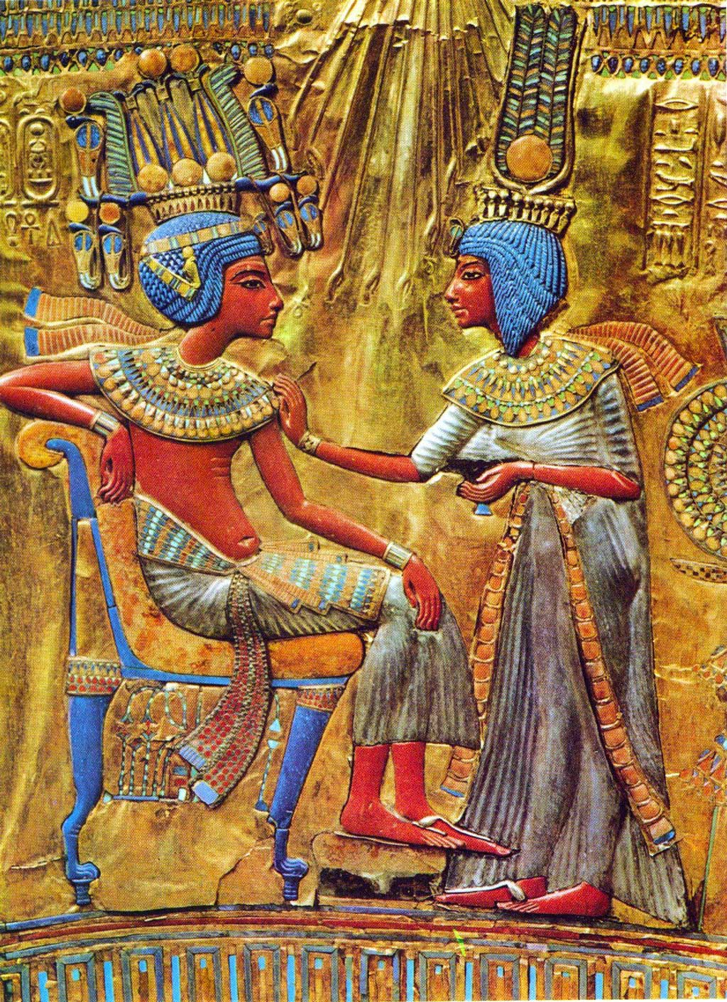 The image comes from the gold-plated throne of Tutankhamun. It depicts the king seated on a couch while his wife, Ankhsenamun, stands before him, touching his shoulder. Both figures are vibrantly colored with umber skin, indigo hair, and grayish-white garments.