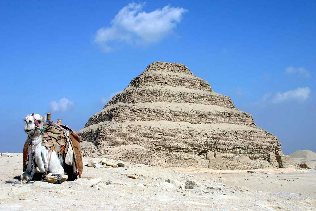 The picture is that of Djoser's stepped pyramid. The pyramid includes five mastabas stacked on top of one another like a pyramidal layer cake. A camel sits in front of the pyramid.
