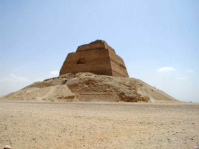 The picture is that of the pyramid of Meidum. Here, a mound of dirt and stone lies around the smooth-sided stone tower within, from which it has rescinded over time.