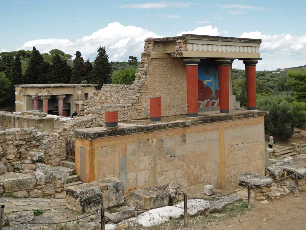 Picture of a stony path leading upwards to the Northern Entrance of the Palace of Knossos. On the top level are the remains of bull fight fresco behind three crimson columns.