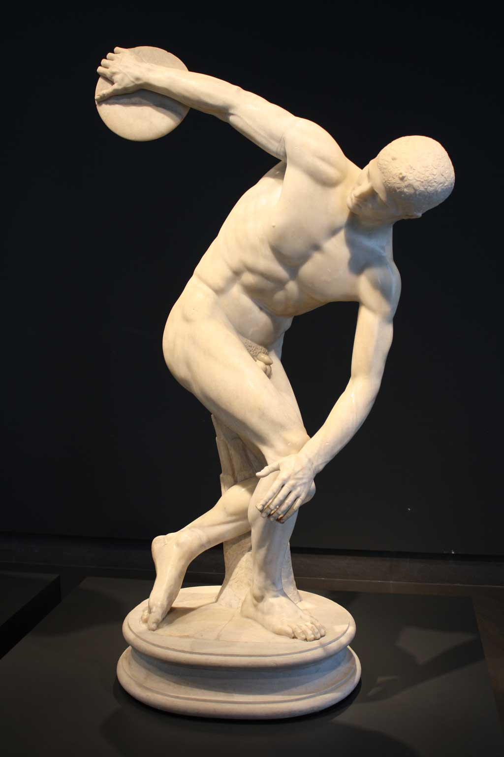 Image of the Discus Thrower. A marble replica of the original, the statue depicts a stoic-faced athlete in mid-rotation as he prepares to hurl the discus aloft.