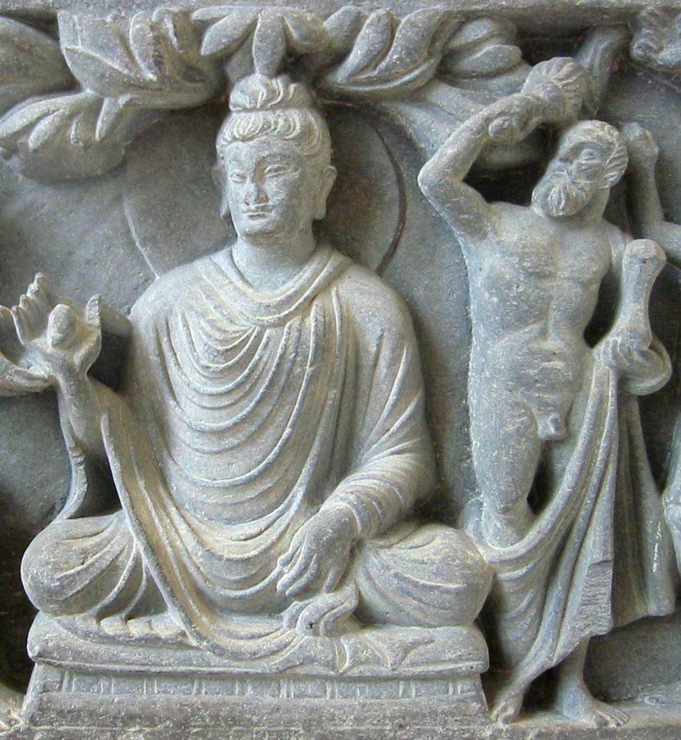 Stone relief of the Buddha sitting in the lotus position with long flowing robes. Positioned to the Buddha's left is a strapping depiction of Hercules holding a mace in his right hand to signify his role as the Buddha's protector.