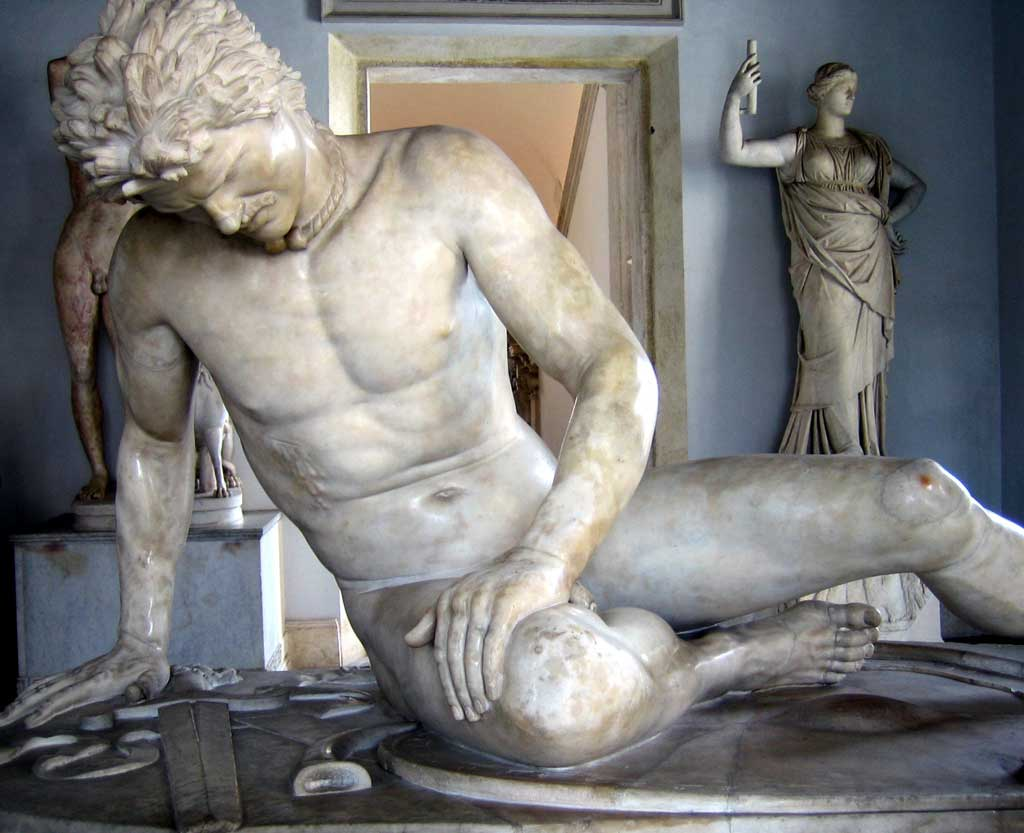 Marble statue of the Dying Gaul.From this angle, the man sits with head tilted downward, hunched over in pain from a blade wound just below his breast.