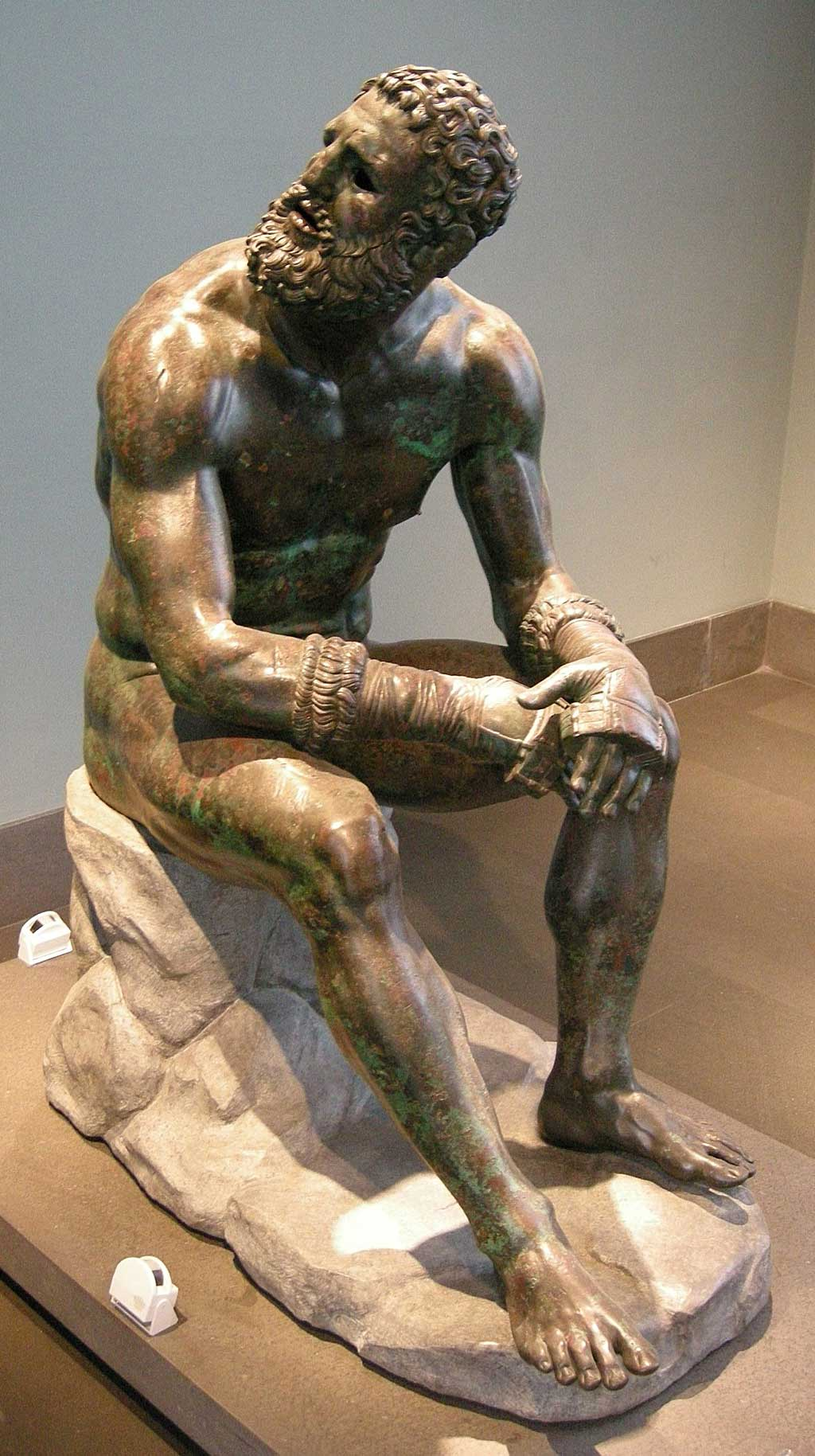 Image of the Boxer statue. The bearded man sits on a stone, looking upwards while wearing the leather gloves still strapped around both hands.