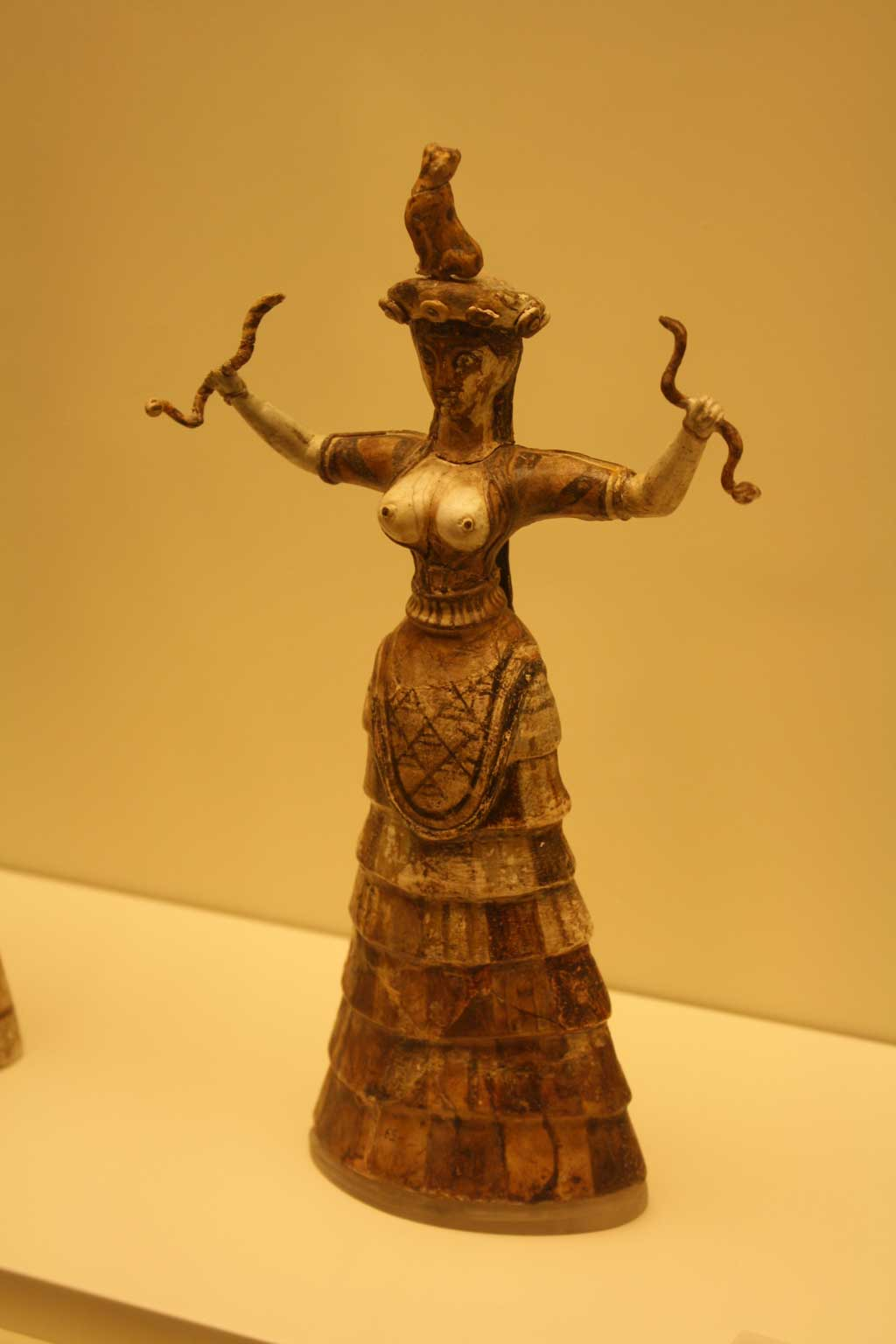 Knossos figurine of a bare-chested woman holding a slithering snake in each hand.