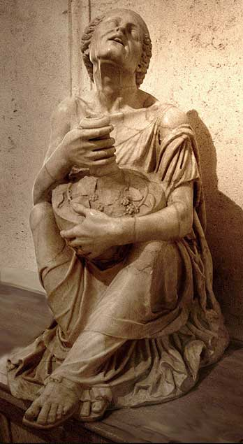 Image of the marble Drunken Woman statue. The woman sits on the ground with feet crossed forward while grasping a large vessel of wine in her two arms.
