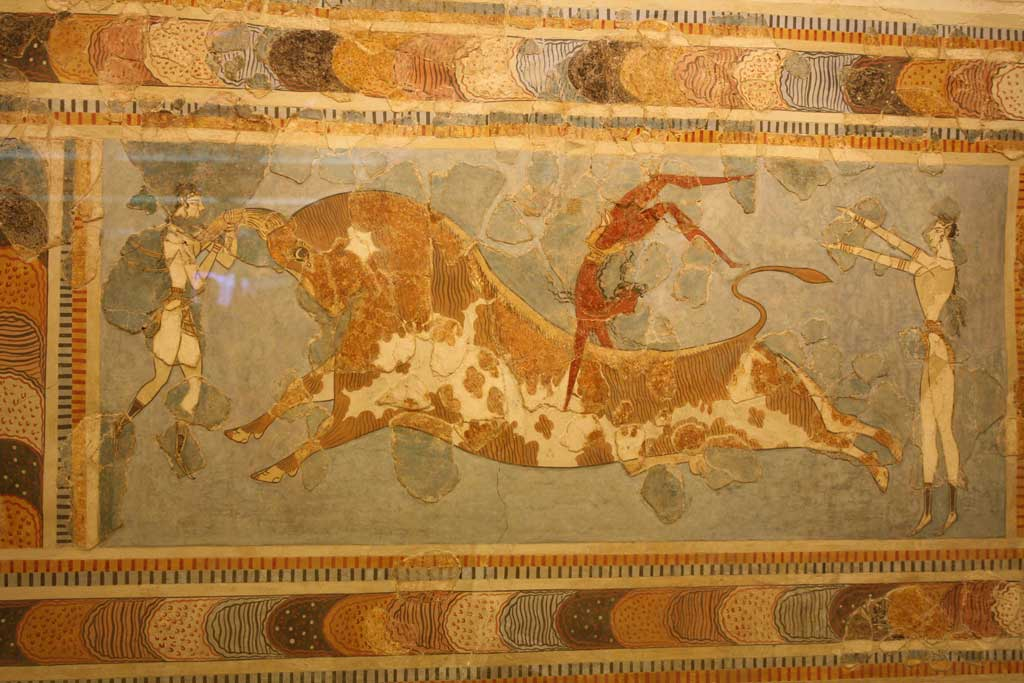 Fresco from Knossos depicting a brown-skinned performer somersaulting over a large bull with the aid of two light-skinned assistants. The fresco may indicate that Knossos was a multi-cultural society.