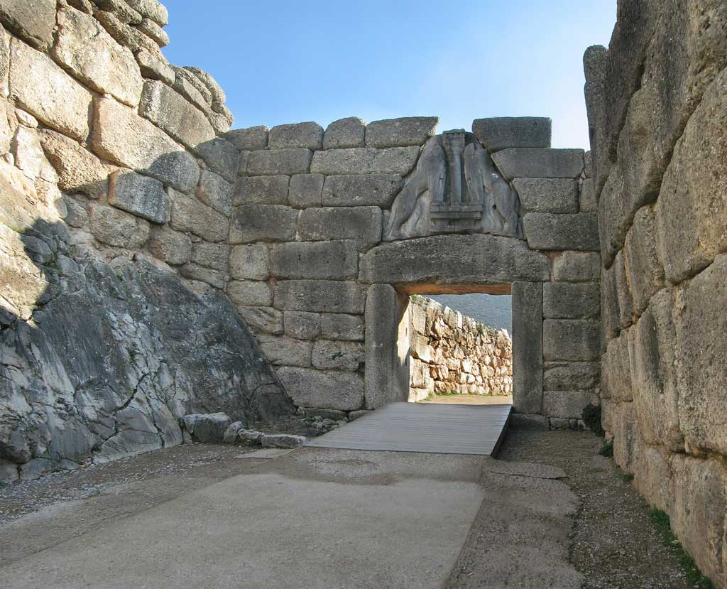 Picture of the Lion Gate from Mycenae. The walls surrounding the gate are comprised of enormous rectangular stone blocks. Two lions site another atop the gate under which visitors entering the city must pass.