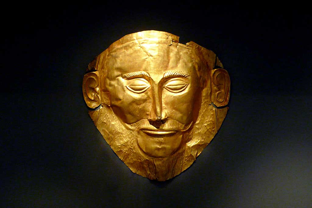 Image of a gold mask depicting a bearded man with closed oval eyes, long slanted nose, and pronounced ears.