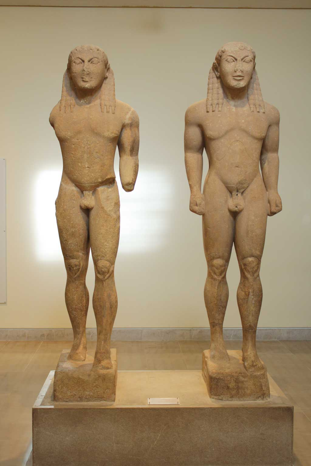 Picture of two nude male statues carved from sand stone. Like earlier Egyptian statues, these two figures are standing upright and face forward with arms to their side, and one foot positioned ahead of another.