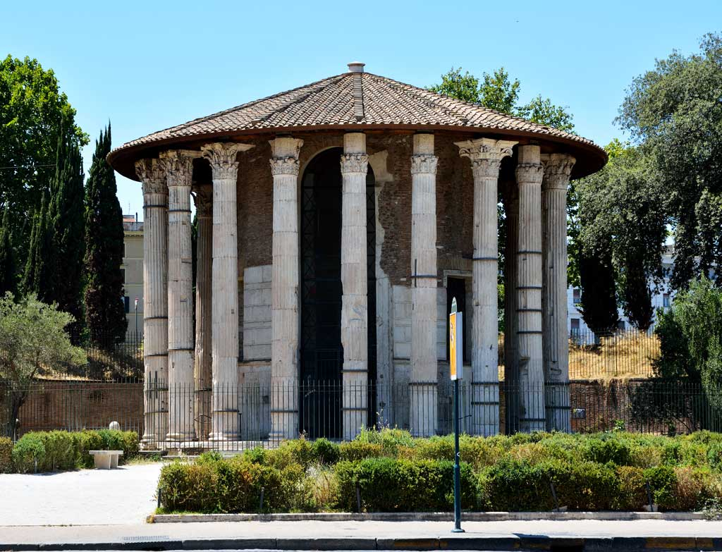 This photo shows the ruins of the Temple of Hercules Victor. It is a circular facility with a slanted rounded roof. It is surrounded by columns on a platform.
