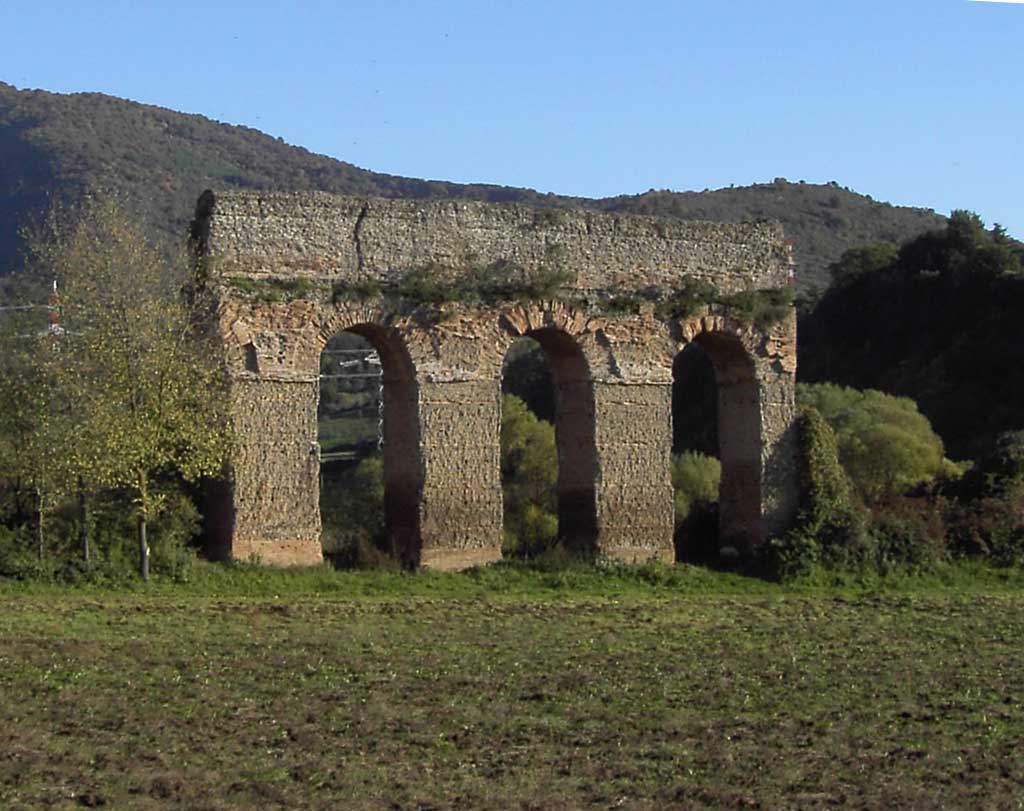 Picture of the Aqua Marcia standing in an open field. Only four arches of the concrete aqueduct remain.