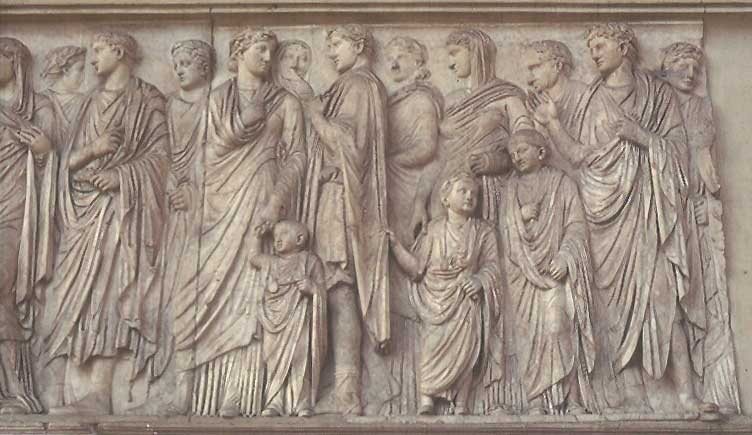 This photo shows a detail from the processional scene on the south wall of the Ara Pacis Augustae. In the center stands Augustus next to his wife Livia. Their family stands behind the couple on all sides. The figures ascend from the wall giving them a three-dimensional quality.