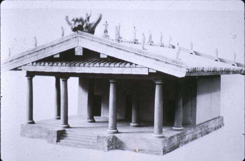 Picture of a model Etruscan temple. The temple has a slanted roof stationed atop eight columns and an inner chamber. The temple itself sits atop a porch with staircase.
